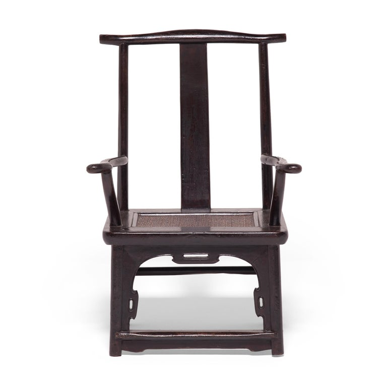 Unusual for its small scale, this pair of 19th century tall back chairs are diminutive updates on the classic yoke-back armchair popular since the Song dynasty. Also referred to as official's hat chairs, the chair mimics the brimmed hats of