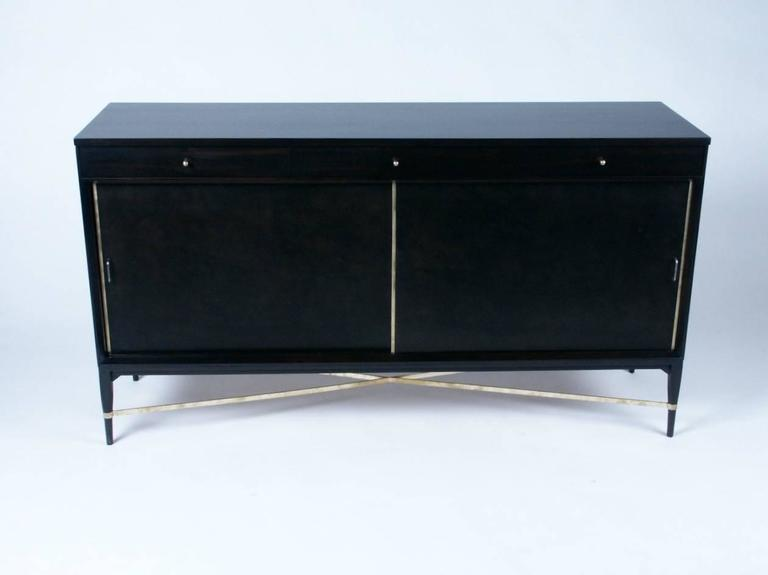 Paul McCobb sideboard, three drawers at top, sliding leather doors with brass trim, and adjustable shelves, brass X stretcher between tapered legs. Currently being refinished in dark espresso.