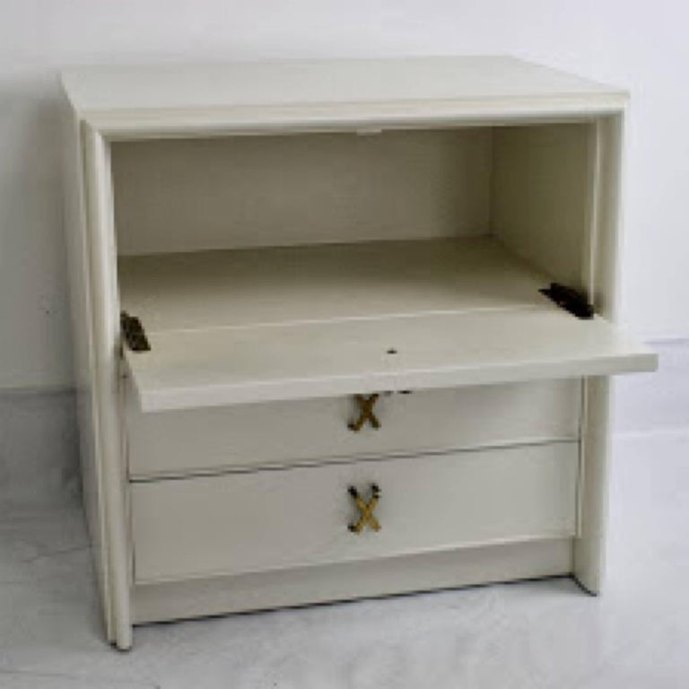 Pair of nightstands or small chests, designed by Paul Frankl for Johnson Furniture. Shown in ivory lacquer but can be finished in custom color with wood stain. Top drawer has drop down feature as a writing surface. Two bottom pull-out drawers below.