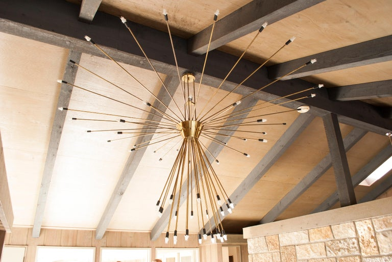 Iconic and possibly one of a kind, monumental scale of 9' diameter x 6' high, 60-arm brass chandelier in the form of a Sputnik satellite. Removed from the home of one of the founding family members of Bussmann Fuse. This fixture once hung in a
