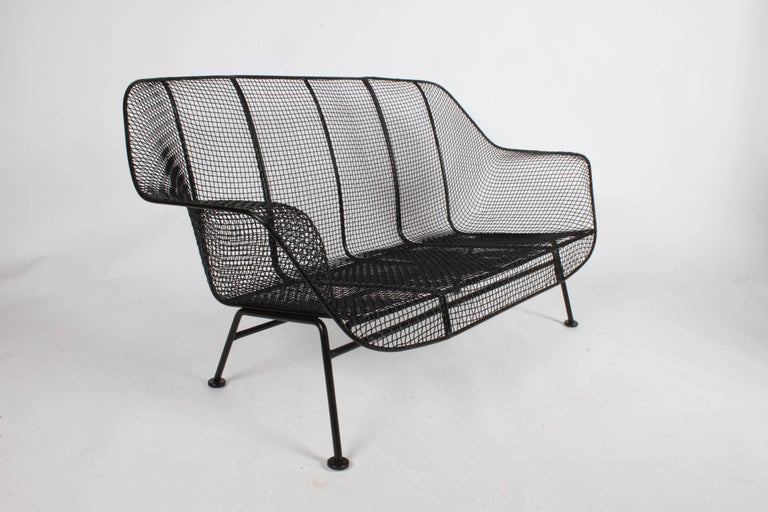 Russell Woodard designed sculptura wrought iron mesh settee. This settee has just been restored, sandblasted, dipped in rust coating and sprayed with satin black. New glides added to feet. This form reminds me of Eero Saarinen's womb chair.