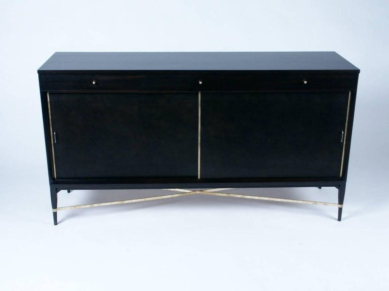 Paul McCobb sideboard or credenza, three drawers at top, sliding leather doors with brass trim, and adjustable shelves, brass X-stretcher between tapered legs. Currently being refinished in dark espresso, custom color available.