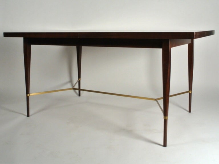 Philippine Mahogany dining table with brass X stretcher between tapered legs, designed by Paul McCobb, part of his Irwin collection for Calvin. Includes two 12