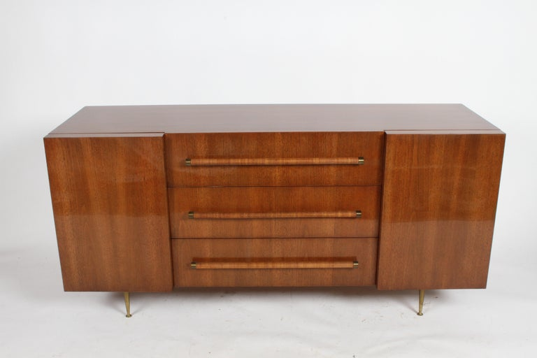 Rarely seen elegant T.H. Robsjohn-Gibbings for Widdicomb sideboard or dresser. Completely restored cabinet to original color with heavy build hand polished clear coat. Walnut cabinet with center drawers with rattan circular handles with brass end