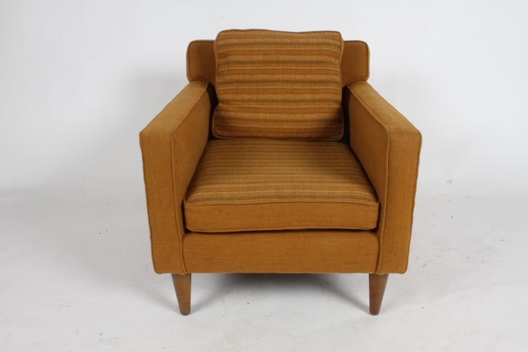 Single Edward J. Wormley for Dunbar club chair with older re-upholstery on thick tapered legs. Unrestored, ready for new upholstery, legs show age, should be refinished. Email for upholstery and refinishing of legs quotes. Has loose back cushion.