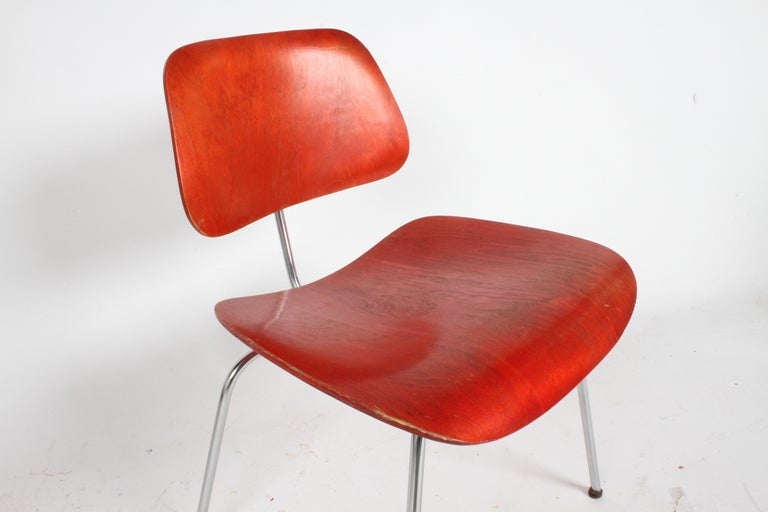 Early Charles Eames for Herman Miller red Aniline stained DCM with early glides, no label. Shock mounts are still solid, there is wear and loss to finish, see photos.