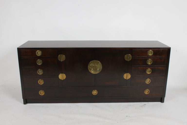 Mid-Century Modern Edward J. Wormley for Dunbar Asian inspired sideboard model # 4579. Mahogany with original dark finish that has been restored, has impressive heavy brass hardware that was imported by Dunbar for authenticity, as noted in Dunbar