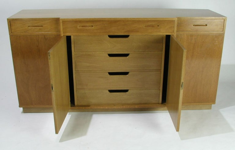 Edward Wormley for Dunbar for modern 1940s bleached mahogany sideboard, center stepped out, inset oval drawer pulls, center interior with drawers and space to store table pads, end cabinet doors hinged on sides and have curved wood door shelves, on