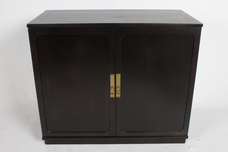 Edward Wormley two-door cabinet in ebonized silver elm with brass Asian Modern hardware, circa 1948. Refinished. There is also a pair of matching cabinets with different hardware available, please inquire. Interior has two sliding drawers over open