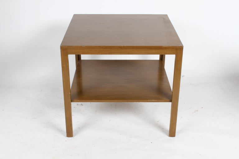 Pair of end tables in walnut, designed by Edward Wormley for Dunbar, early green labels. Currently being refinished (matching two-tiered coffee table also available). The tables show in dark finish are sold, please see others shown in photos, to be