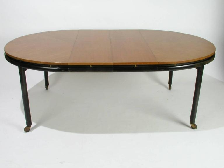 Oval dining table designed by Winsor White and Michael Taylor for Baker's New World collection, circa 1950s, ebonized finish on legs, brass castors, top is given floating effect by vertical brass cylinders set into frame, top is medium light wood