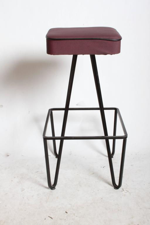 Pair of Frederick Weinberg style wrought iron bar stools. Older upholstery and now only two yellow ones available, eggplant ones sold. Black paint on frames shows minor wear, to be expected.