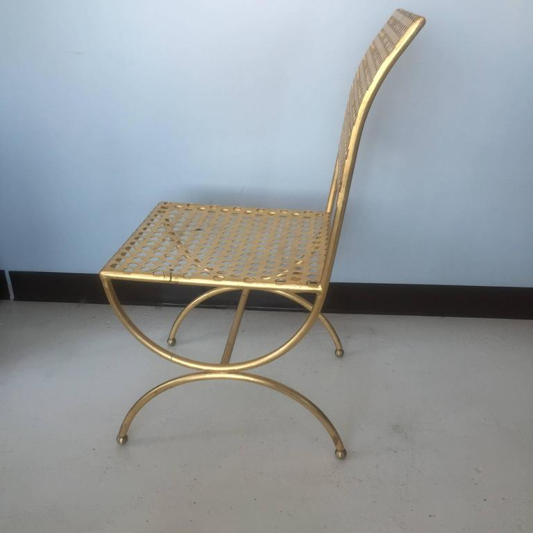 Perforated gilt iron chair designed by Tony Duquette in the 1960s, produced for Baker circa 2011.