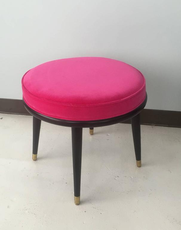 Pair of round stools with tapered legs and brass sabots.