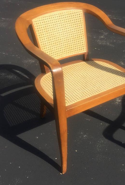 Pair of 1950s Mid-Century Modern armchairs, cane inset seats and backs on walnut frames with splayed legs. In the style of Edward Wormley for Dunbar.