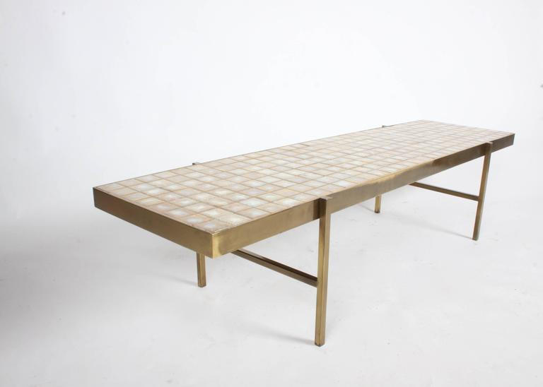 In the style of Edward Wormley for Dunbar, rectangular coffee table with Natzler like crazed gold and white tiles. Nice scale to solid brass frame and legs, very heavy table! Overall great condition, with nice patina. Some minor loss to grout in