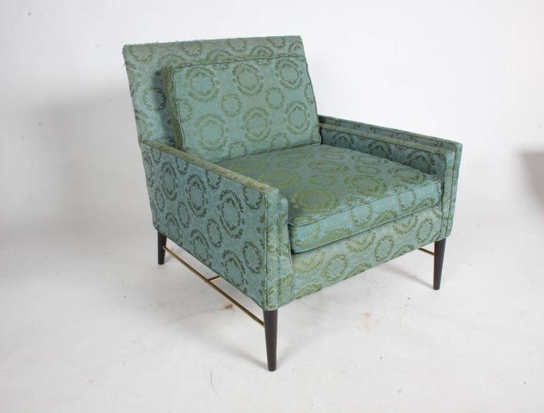 Pair of Paul McCobb for Calvin lounge or club chairs in the original fabric with brass stretchers and tapered wood legs. The brass has been polished and the legs refinished in a dark espresso finish. Upholstery and foam are original, shows wear,