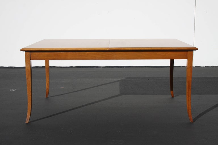 T.H. Robsjohn-Gibbings for Widdicomb saber leg dining table with built in leaves and beveled edge. Original sherry finish show wear and age, price includes refinishing. Can be refinished to match original finish or can be made dark with an espresso