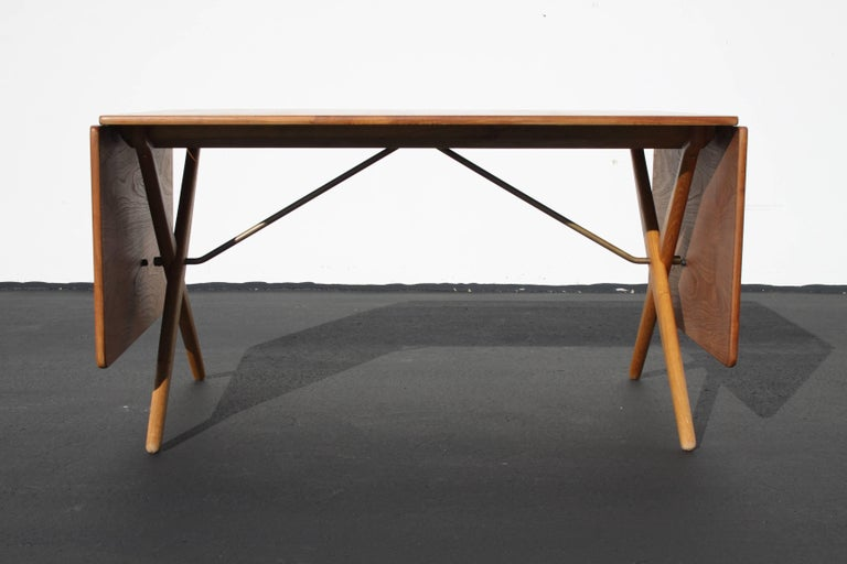 Vintage Danish modern Hans Wegner model AT-309 teak and oak drop leaf dining table. Beautifully restored top and X-legs with great original patina to the brass. Stamped with makers mark Fabrikat: Andreas Tuck, Arkitekt: Hans J. Wegner Denmark. Fully