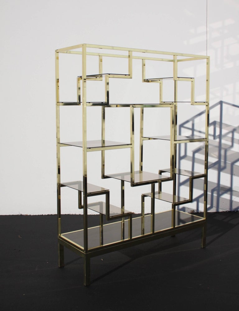 Great looking large Mid-Century Modern brass geometric Italian étagère display with bronze glass shelves. In the style of Mastercraft, Milo Baughman or Romeo Rega. In very nice condition, brass has some minor patina in areas, otherwise very nice.