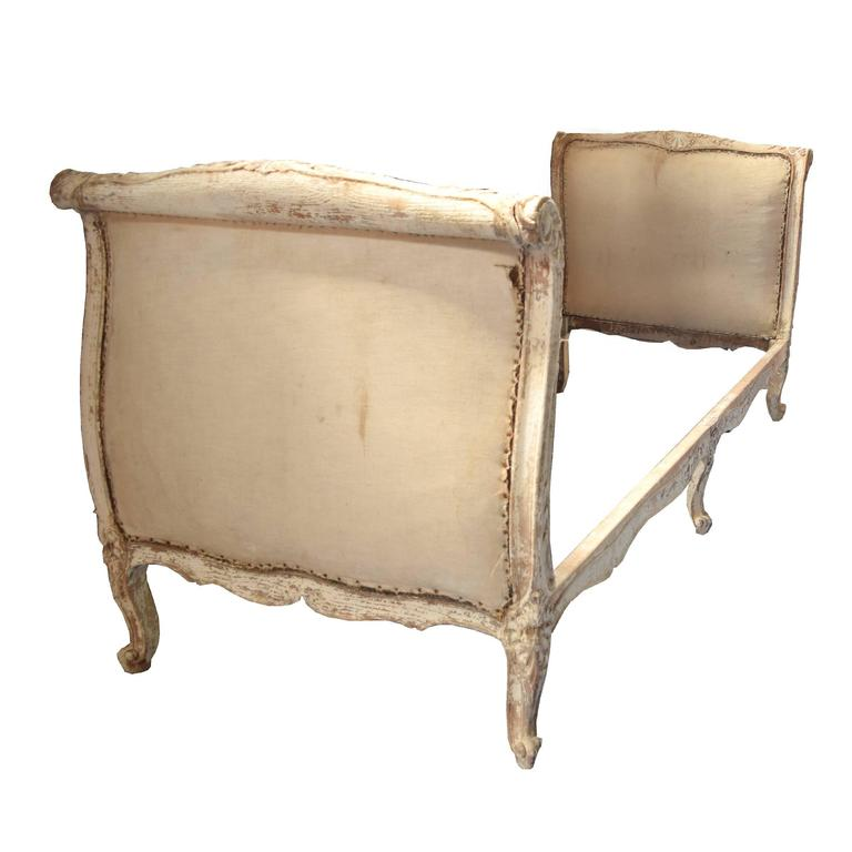 A lovely French Louis XV style carved wood daybed with original paint and muslin upholstered headboard and footboard. Gorgeous patina, 19th century.