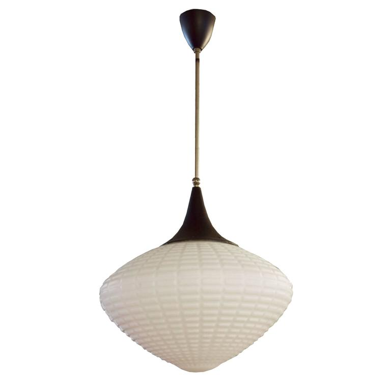 A Mid-Century Czech pendant light fixture with a brass downrod and opaque molded glass shade. Many available. Need to be re-wired.