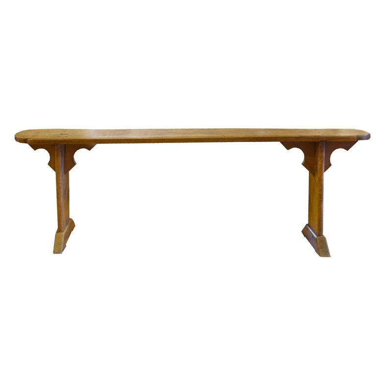 A pair of French walnut plank top benches with two legs and decorative spandrels, 19th century.