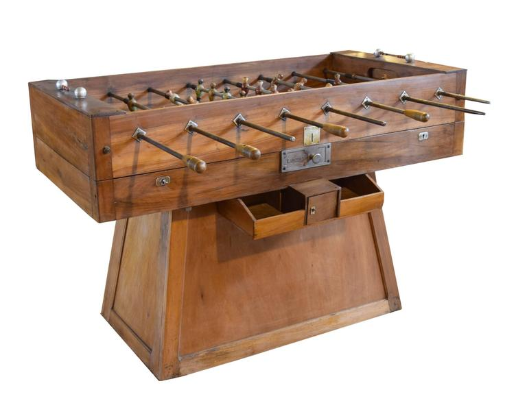 A coin operated wood foosball table from Italy. This circa 1930s table is an early example of a foosball table given that they were first invented in 1922. The original wooden players are painted red, green and white.