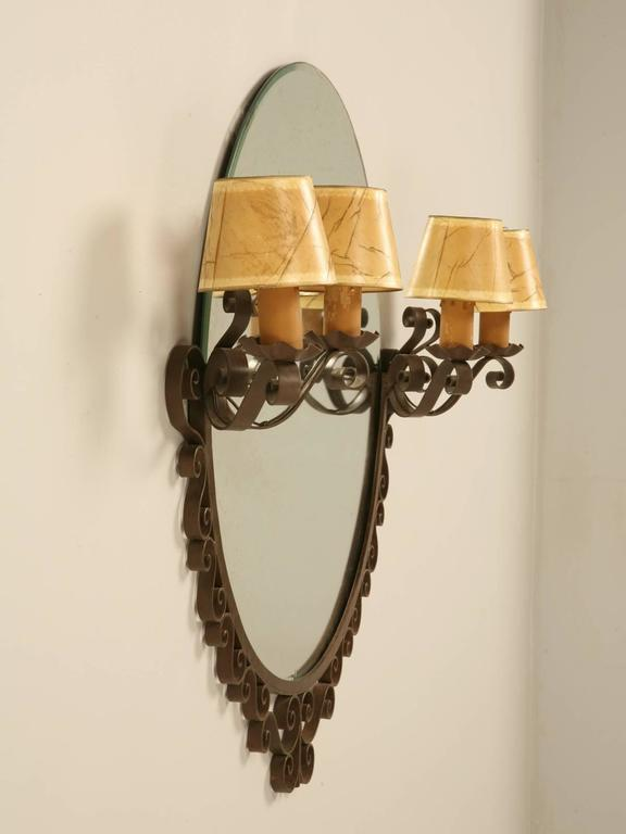 French Art Deco mirror from the 1930s in a steel frame with the original aged glass. Flanked by two pairs of sconces that makes it ideal for a bathroom. Rewired and ready to install.
