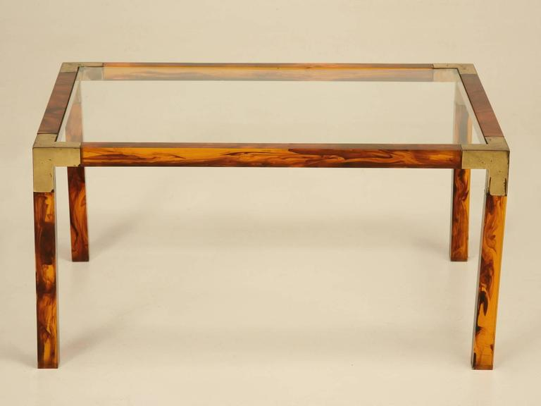 Faux tortoise shell acrylic and brass petite French coffee table. This has to be one of the most unusual and elegant tables we have ever had and I am sure they were mass produced, but we have never seen one before. Please note the patination on the