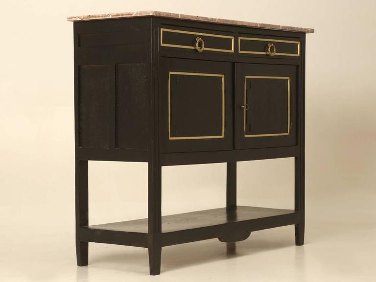 French Louis XVI style ebonized small two-door server, with a lower shelf and marble top. Our Old Plank finishing department just completed a very nice ebonized finish, so there are no scratches to worry about and there are no previous repairs to