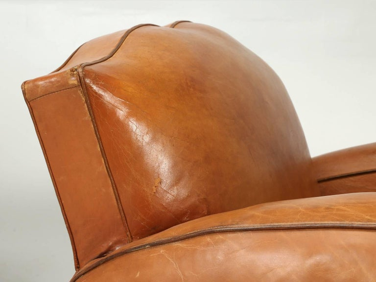 French Moustache style Art Deco pair of original leather club chairs, that our Old Plank upholstery department stripped down to the bare frame and rebuilt the club chairs correctly. This encompasses, re-gluing the wooden frame, installing eight-way