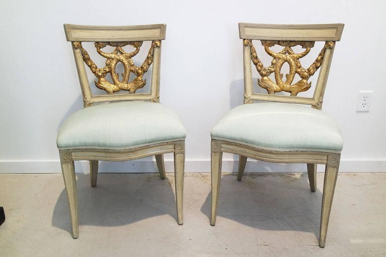 A pair of Italian neoclassical painted and partial gilt side chairs. Last quarter 18th century with dolphin and foliate swags.