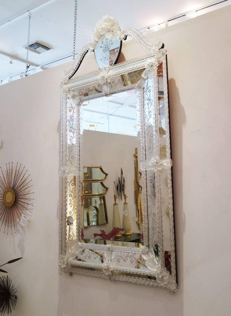 Elaborate clear Venetian mirror with engraving and ruffled leafy edge.