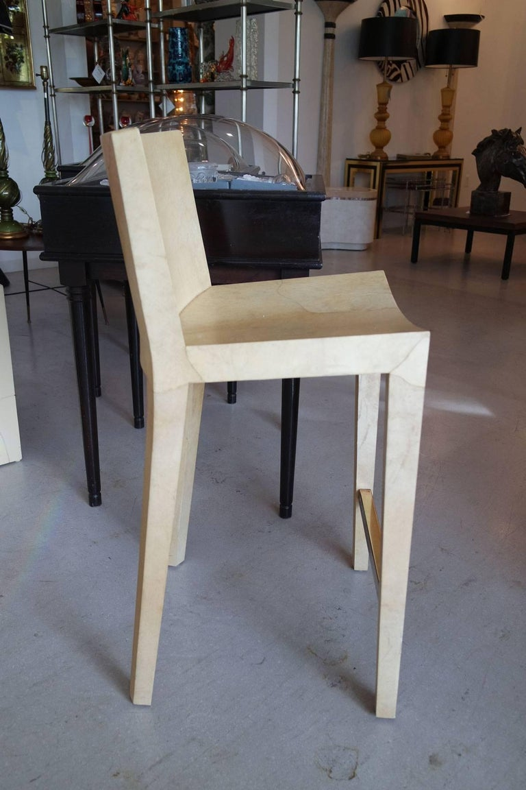 """Five individually priced lacquered goatskin """"JMF"""" bar-stools with brass foot rests by Karl Springer."""