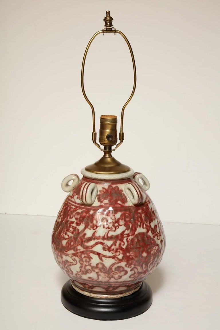 An antique Chinese earthenware vessel red and natural glaze, fitted for electricity, new ebonized base, in working order, does not include shade.