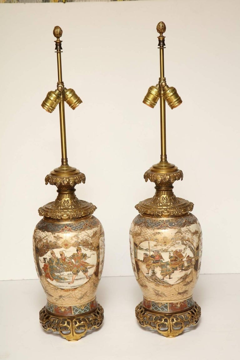 A pair of Japanese Satsuma bronze-mounted table lamps, painted and enameled with vingettes depicting geishas and samurai, with beautifully detailed bronze mounts, in working order, does not include shades  The porcelain- Meiji period early 19th
