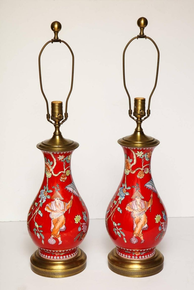 A pair of oriental style porcelain table lamps, depicting flowering branches, monkeys and figures at leisure, with gilt-brass base and vase cap, new standard wiring.