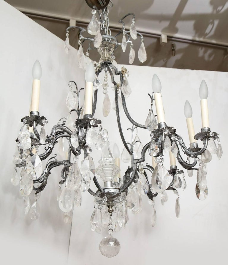 Silvered-metal Louis XV style chandelier, the cage-form frame issuing 12 candle-arms, electrified.
