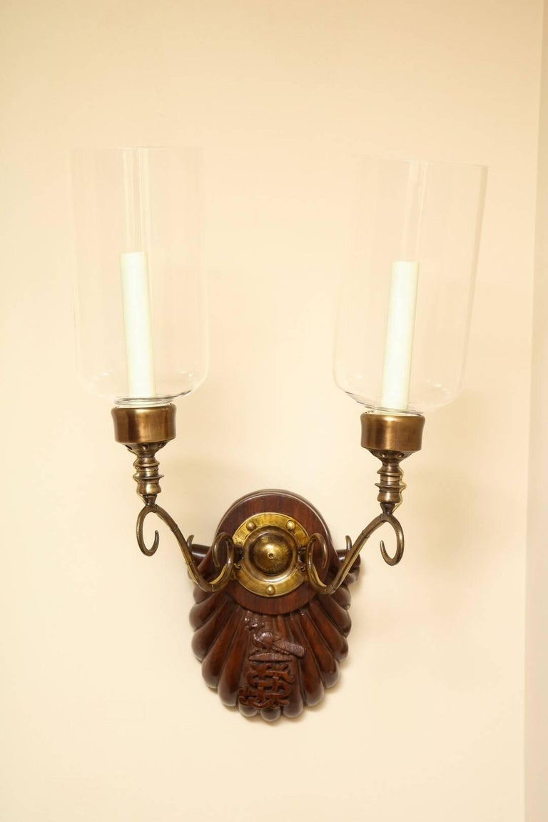 A pair of engraved Anglo-Indian two-light sconces, hardwood shell form back-plate issuing bronze out-scrolled candle-arms supporting a single Edison socket with hurricane shade, circa 1890. Maximum wattage per socket 100W.  Provenance: These