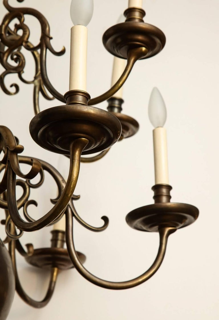 A twelve-light Dutch Baroque style patinated bronze chandelier with ball shaped element, below two tiers of candle arms.
