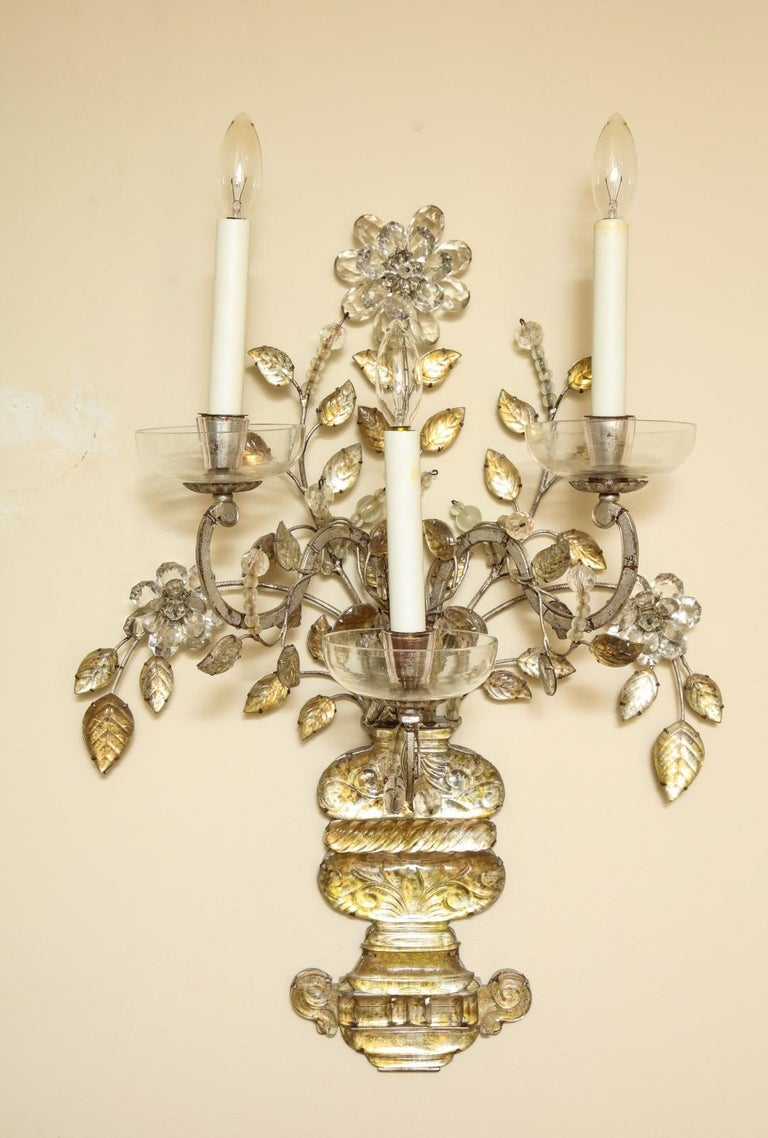 A pair of three-light sconces, silvered metal with glass vase issuing vinery and scrolled candle arms, attributed to Maison Baguès, circa 1920.