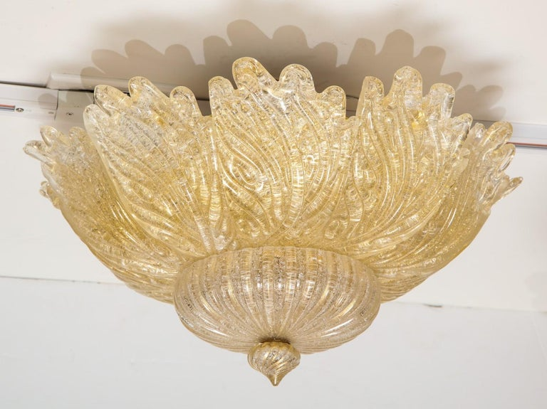 A Venetian Murano flower form ceiling light, handblown leaf-form golden powder glass panels, centring a spiral form finial.