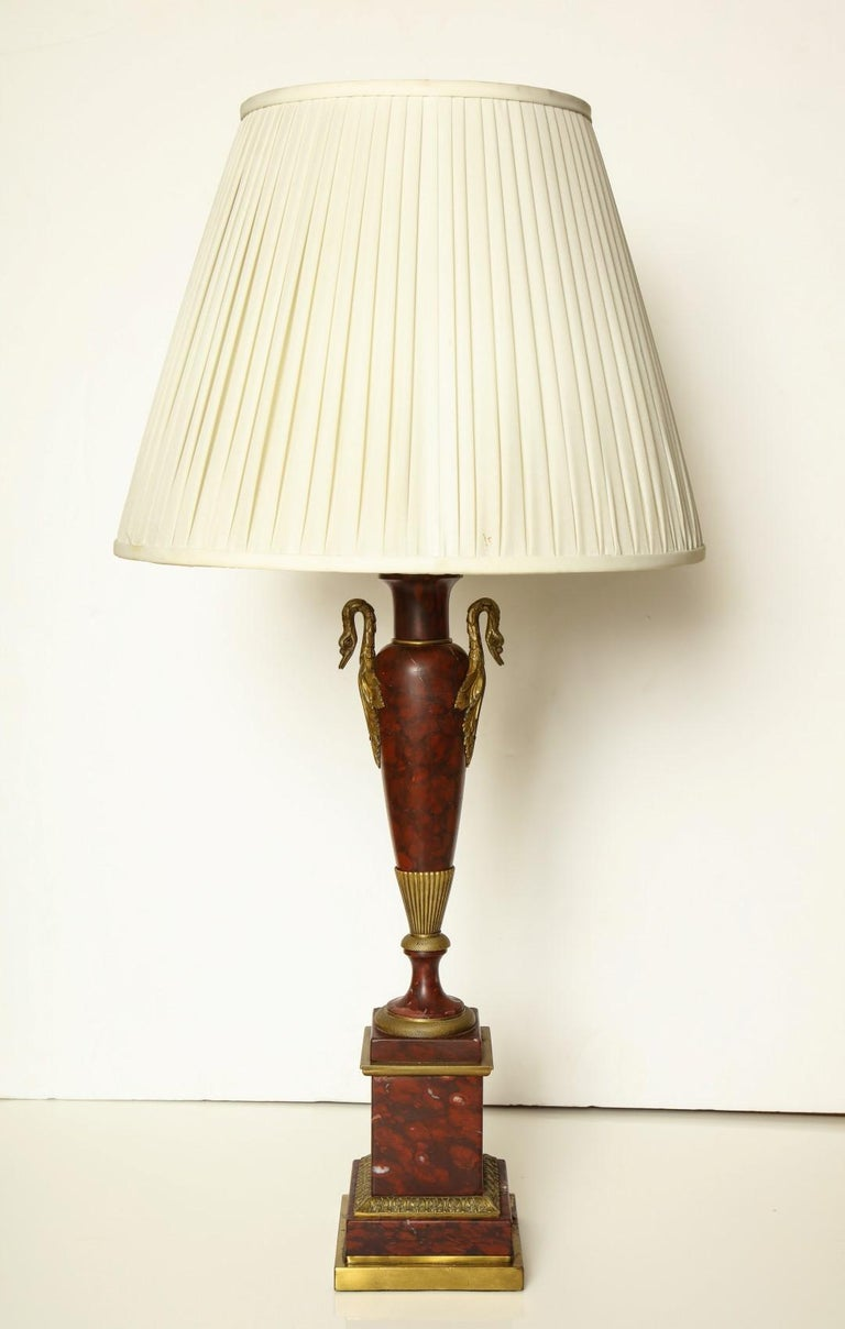 Neoclassical style bronze mounted columnar table lamps, stepped rouge marble plinth supporting a stem with swan neck terminals and spreading socle foot