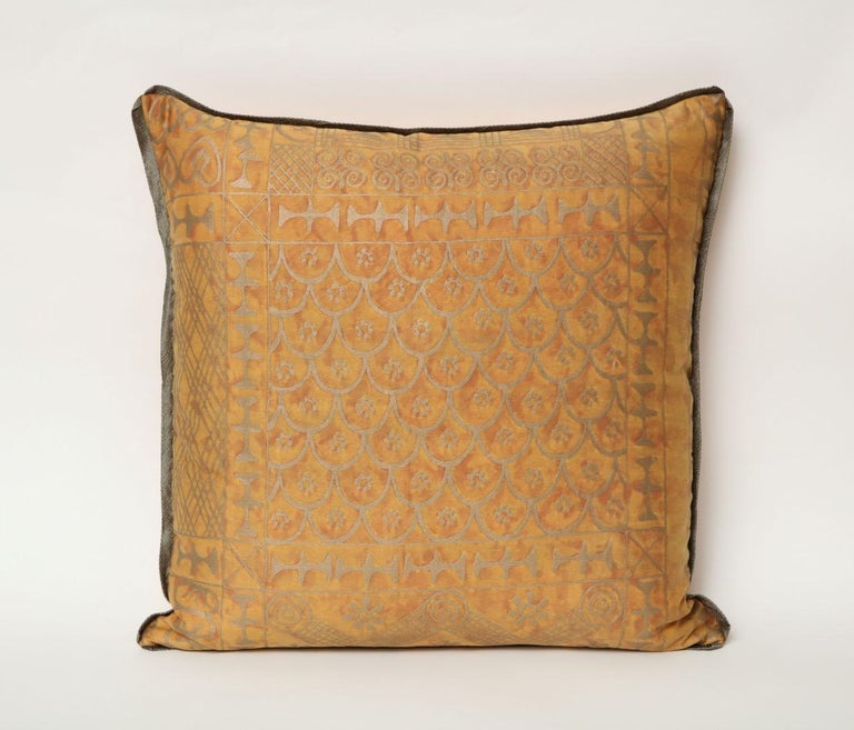 A pair of vintage Fortuny fabric cushions in the Ashanti pattern, burnt apricot and silvery gold color way with braided edging and silk blend backing, the pattern, a Geometric design with African tribal motif.