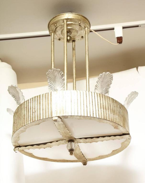 An Art Deco inspired round ceiling light, secured on the underside by four leaf shaped ornaments, the underside with scalloped edge frame holding white opal glass inserts and with faceted crystal ball finial on underside, the frame of the body