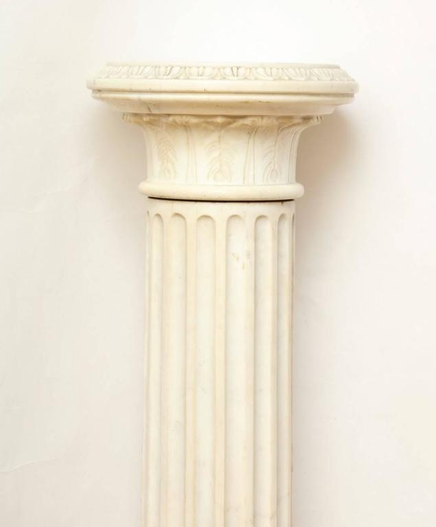 A marble Corinthian capital architectural pedestal, the fluted shaft with an egg and dart wasted socle on a square base, the removable top carved as a Corinthian capital with everted egg and dart rim.