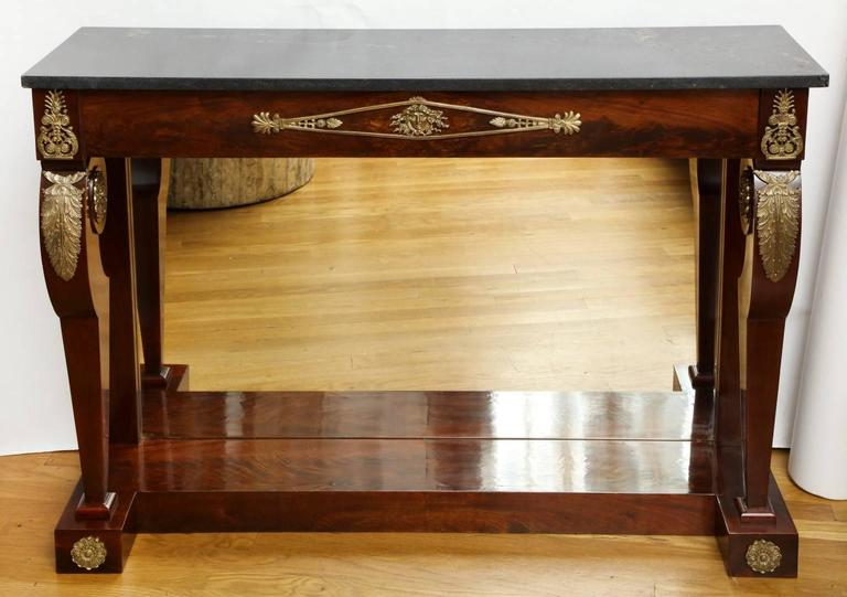 An Empire ormolu-mounted Rosewood Pier-Console, the tapering legs with foliate headed scroll form knees with inset rosettes, black polished stone top with subtle white veining resting on an anthemion mounted frieze with central palmette and gorgon
