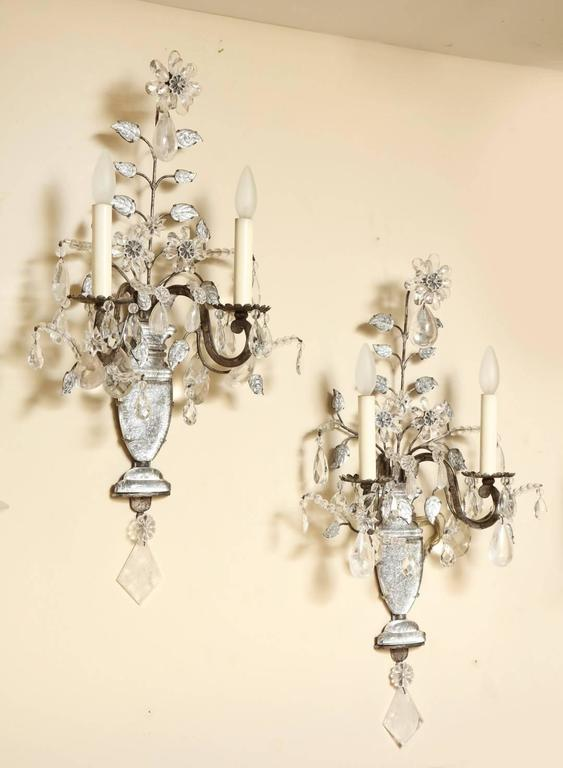 A pair of French Maison Bagues two-light wall sconces with silver gilt iron frames mounted with molded glass vase shaped elements backed with silver leaf. Each backplate issuing branches with individual crystal leaves and flowers formed of crystal