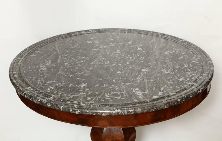 """A Charles X style marble-top occasional table, the original Saint Anne marble top resting on a rich mahogany bulbous pedestal with tripartite scroll form legs terminating in hairy paw feet on castors. Measures: Diameter of tabletop is 32.5""""."""